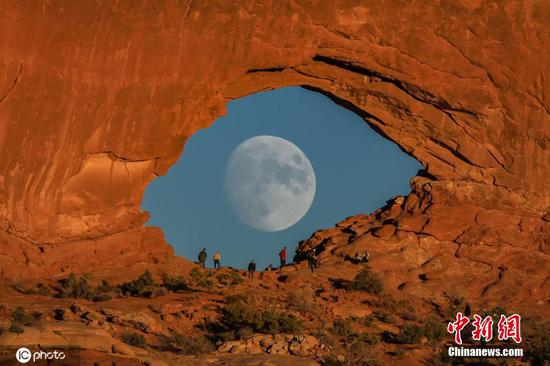 Full moon looking like giant eye in stunning rock arch photograph